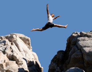 Man leaping over chasm freedom